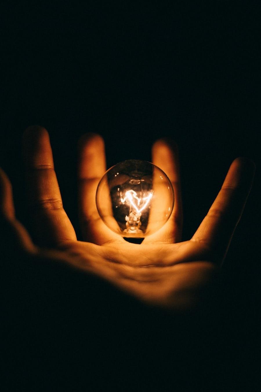 hand with palm facing upwards with a lit light globe in the middle